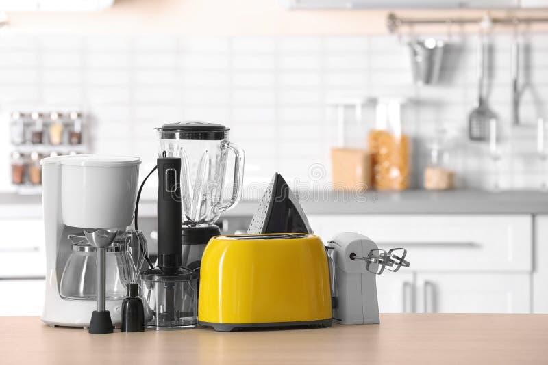 Dispositivos del hogar y de cocina en la tabla foto de archivo