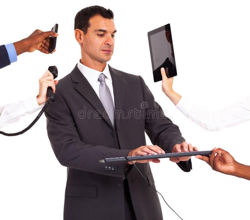 Dispositivos do múltiplo do homem de negócios fotografia de stock