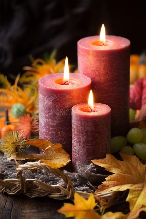 Disposizione autunnale con tre candele e foglie accese di caduta fotografia stock