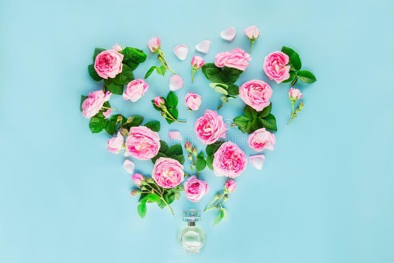 Disposizione creativa con la bottiglia di profumo ed i fiori rosa del tè rosa dentro fotografia stock libera da diritti