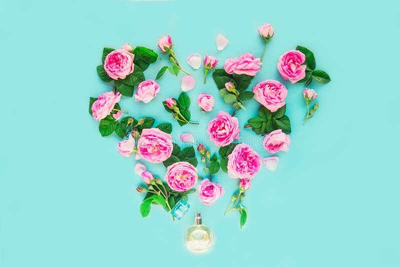 Disposizione creativa con la bottiglia di profumo ed i fiori rosa del tè rosa nella forma di cuore sul fondo del turchese Concett fotografia stock