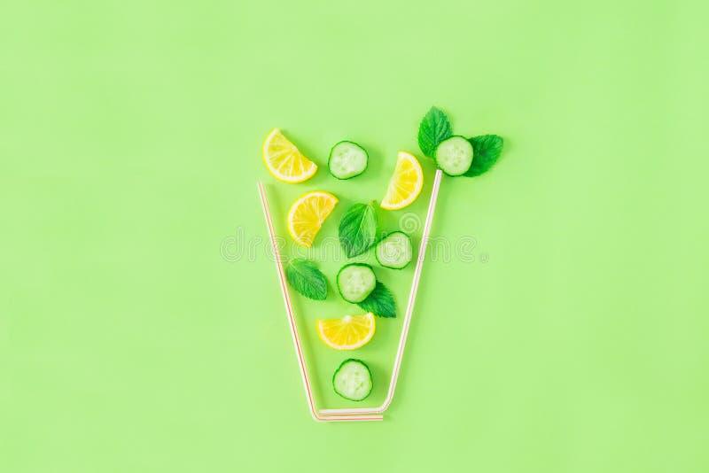 Disposizione creativa degli ingredienti della limonata - il limone, la menta, cetriolo affetta la caduta in vetro fatto con le pa immagine stock