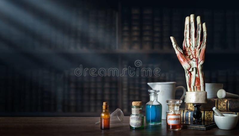 Disposizione d'annata della mano di un uomo, vecchie bottiglie di vetro mediche, strumenti medici antichi sui precedenti di un uf fotografie stock libere da diritti