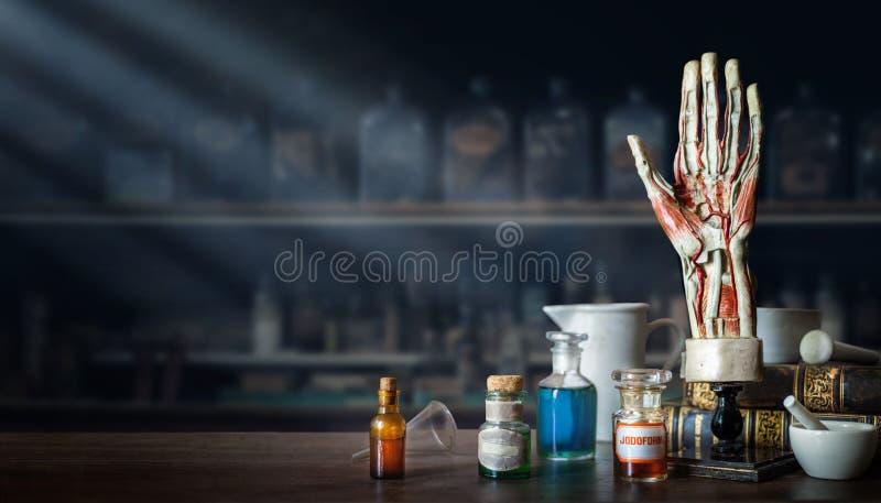 Disposizione d'annata della mano di un uomo, vecchie bottiglie di vetro mediche, strumenti medici antichi sui precedenti di un uf immagini stock libere da diritti