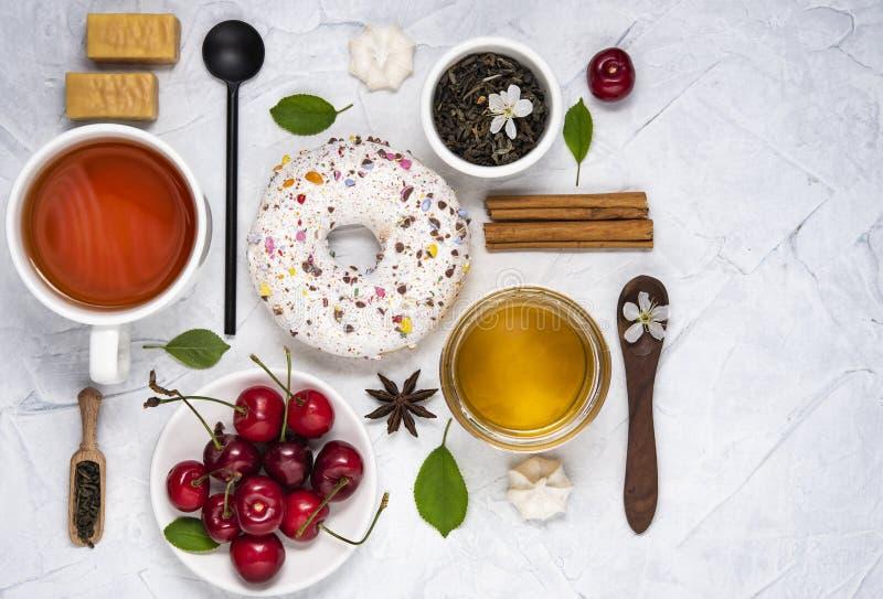 Disposizione del piano con la composizione nella prima colazione del cucchiaio della ciliegia del miele della ciambella del tè su immagine stock libera da diritti