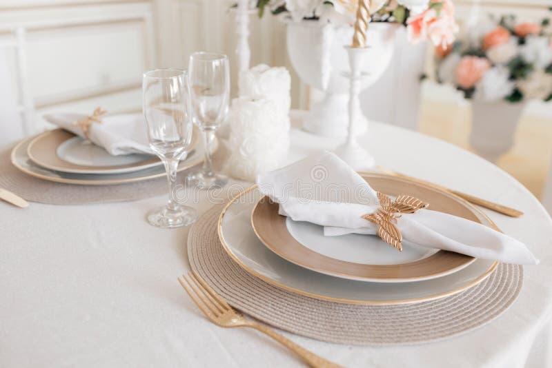 Disposizione del primo piano della tavola festiva tavola e sedie decorate per una cena festiva Decorazione di lusso con luce del  fotografia stock