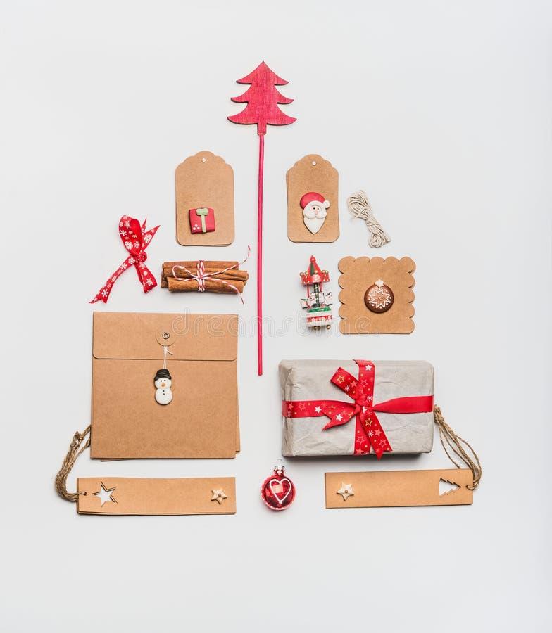 Disposizione dell'albero di Natale fatta con i contenitori di regalo di spostamento di carta del mestiere, le etichette, i giocat fotografia stock