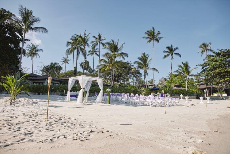 Disposizione della sede di nozze di spiaggia alla spiaggia, all'arco, all'altare con la decorazione minima dei fiori, alla palma  fotografia stock