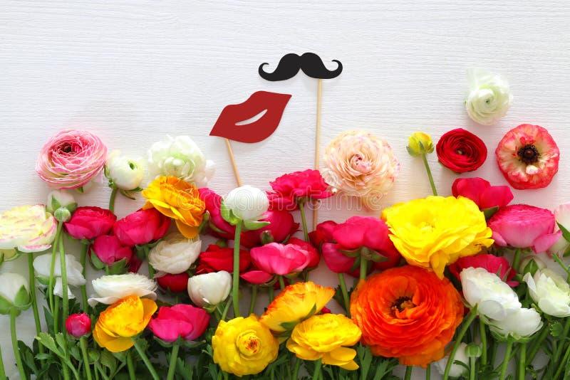 disposizione di fiori, labbra false di carta e baffi in bastoni fotografia stock libera da diritti