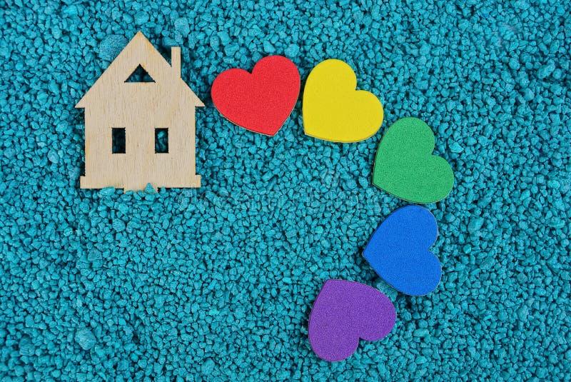 Disposizione di legno della casa e un insieme dei cuori colorati sulla sabbia blu fotografie stock libere da diritti