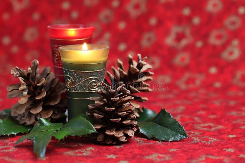 Disposizione di natale con le candele ed i coni immagini stock libere da diritti