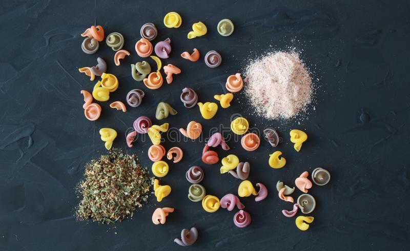 Disposizione di pasta italiana colorata con sale himalayano rosa e pro fotografia stock