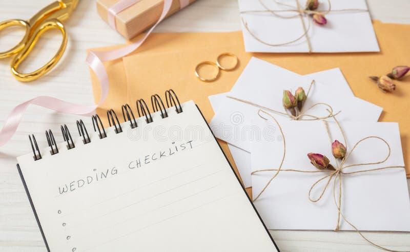Disposizione e fine piane sulla vista degli inviti di nozze e della lista di controllo su un ripiano del tavolo di legno bianco,  fotografia stock libera da diritti