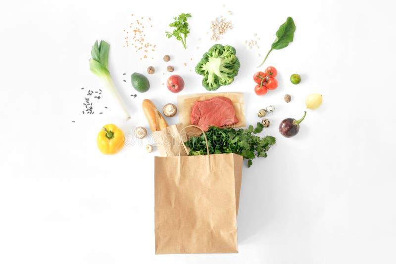 Disposizione piana bianca di vista superiore del fondo dell'alimento sano differente pieno del sacco di carta fotografia stock