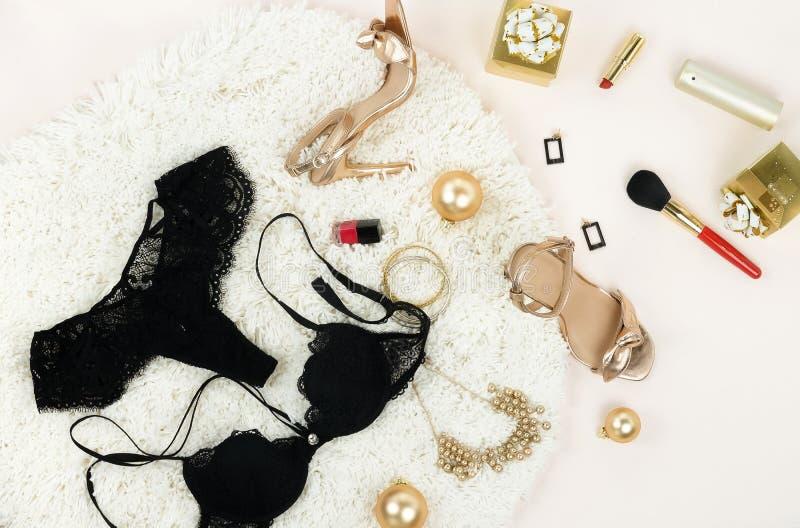 Disposizione piana, biancheria nera femminile di vista superiore, colore dorato dei sandali delle scarpe dei tacchi alti, accesso immagine stock