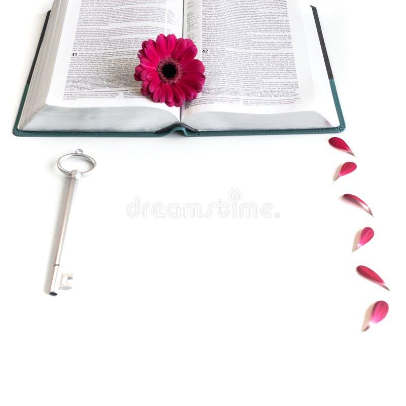 Disposizione piana: chiave aperta della bibbia, del libro, e rosa grigi/d'argento, porpora, violette, fiore rosso della gerbera c immagine stock libera da diritti