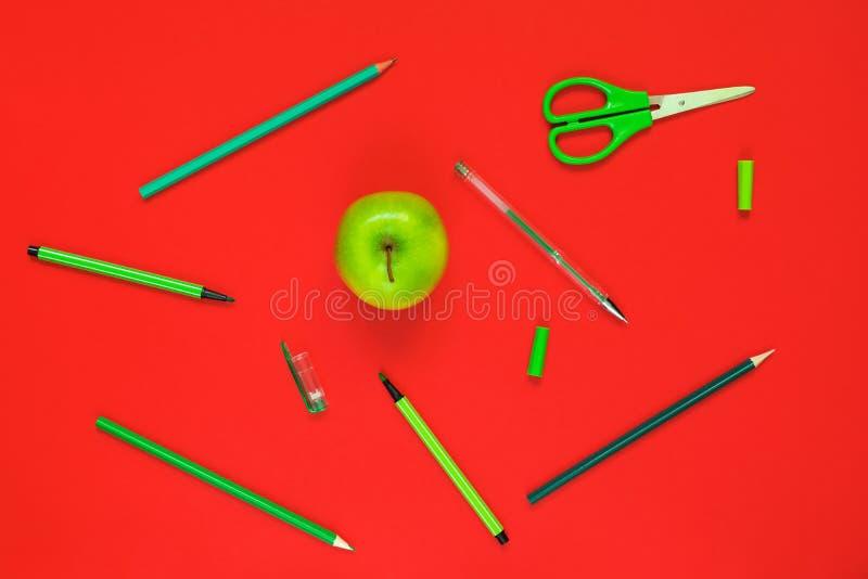 Disposizione piana creativa dei rifornimenti di scuola - penne verdi, matite, forbici e una mela su un fondo rosso fotografia stock libera da diritti