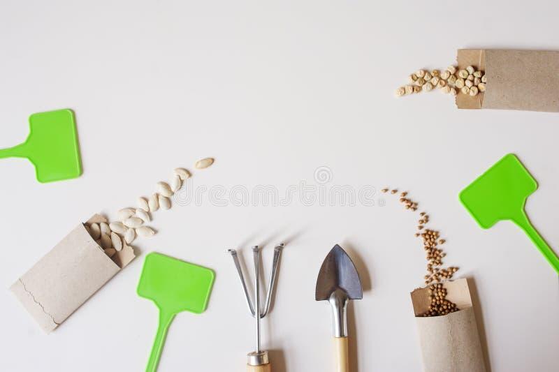 disposizione piana del lavoro del giardino della molla con i semi di verdure in buste fatte a mano immagini stock