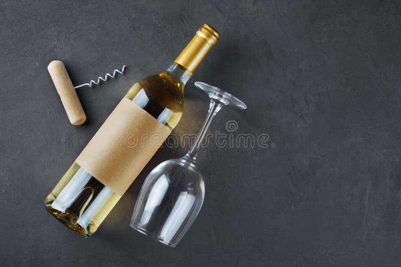 Disposizione piana della bottiglia di vino bianco di menzogne con l'etichetta, la cavaturaccioli ed il vetro vuoti per avere un s fotografia stock
