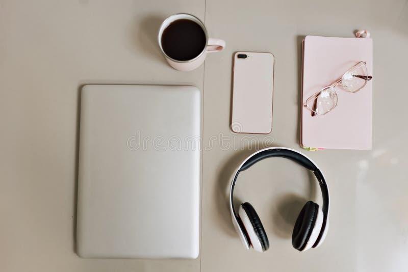 Disposizione piana dello scrittorio funzionante delle free lance alla moda moderne con un computer portatile, uno smartphone, le  fotografia stock libera da diritti