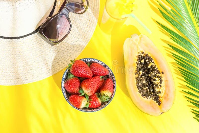 Disposizione piana di disposizione del vetro alto degli occhiali da sole del cappello con frutta tropicale fresca Juice Papaya St fotografia stock