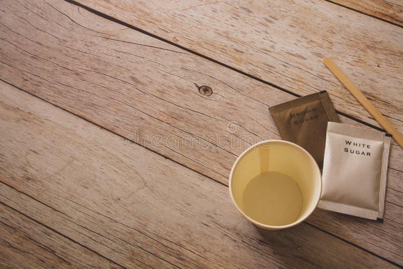 Disposizione piana di derisione vuota sulla tazza di Libro Bianco con le borse dello zucchero bruno e bianche e bastone di legno  fotografia stock libera da diritti