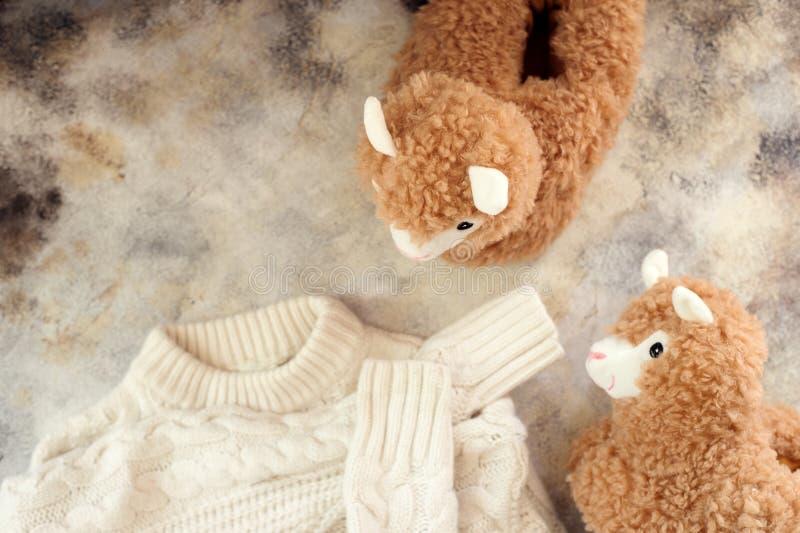 Disposizione piana di inverno accogliente con il maglione bianco della lana e le pantofole d'avanguardia del lama fotografia stock libera da diritti