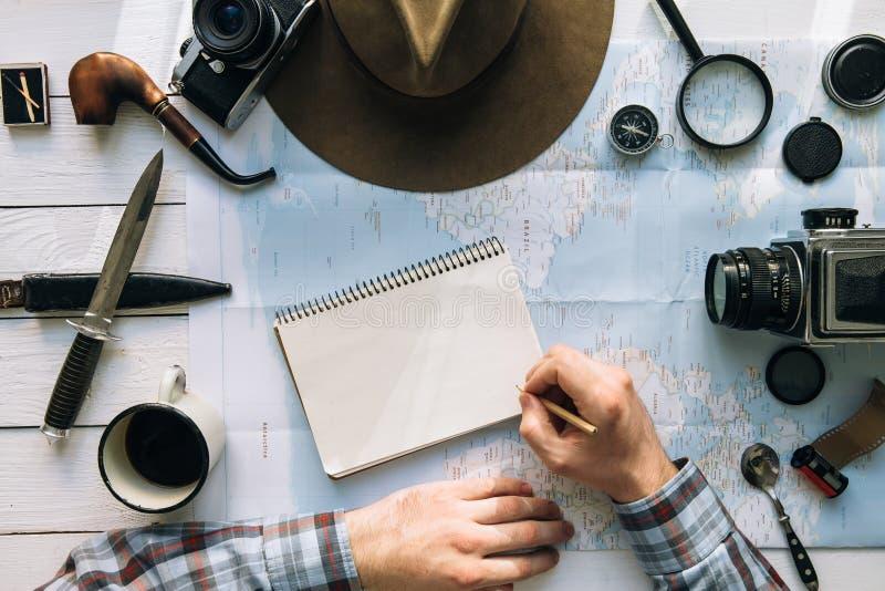 Disposizione piana di pianificazione di avventura Ingranaggio d'annata di viaggio sulla mappa Mani dell'uomo nella scrittura dell immagine stock libera da diritti