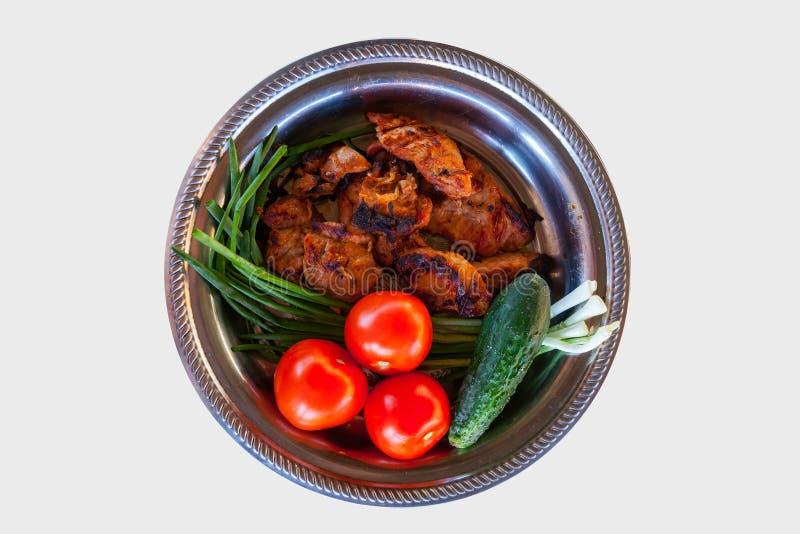 Disposizione piana di un piatto d'argento con la carne dorata arrostita del manzo o della carne di maiale con la crosta bruciata, immagini stock