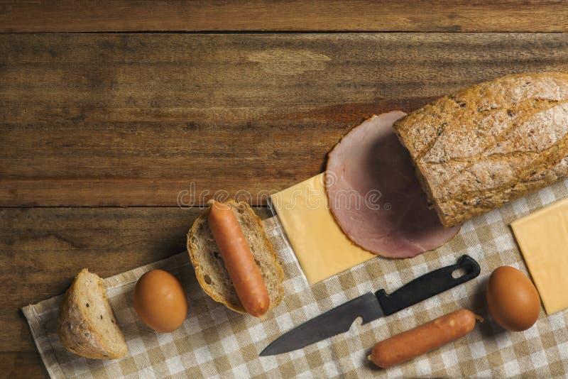 Disposizione piana di vari ingredienti per la prima colazione su fondo, su pane, sull'uovo, sulla salsiccia, sul prosciutto e sul fotografie stock