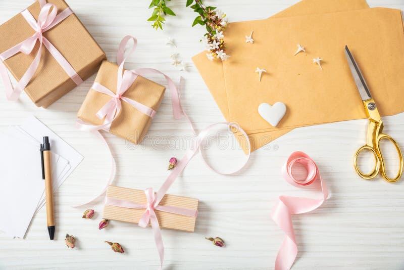 Disposizione piana e vista superiore dei contenitori e degli inviti di regalo su un ripiano del tavolo di legno bianco fotografie stock
