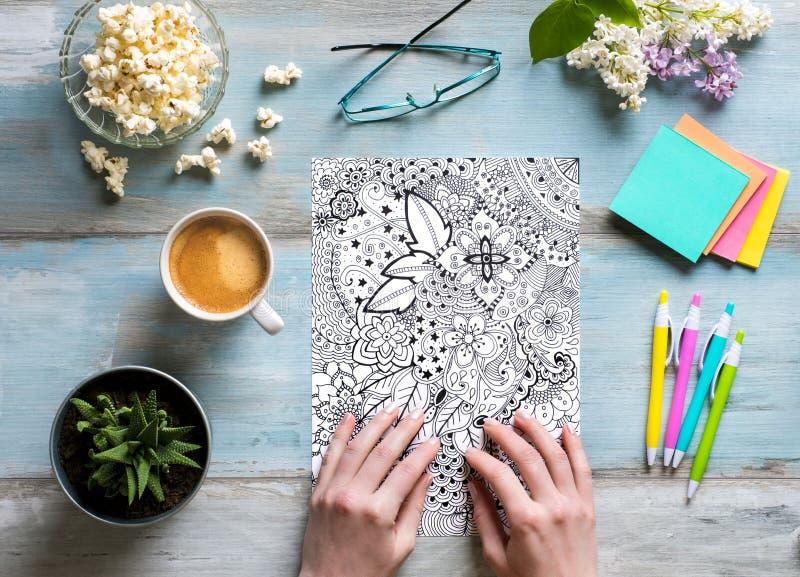 Disposizione piana, libri da colorare adulti di coloritura femminile, tendenza di alleviamento di sforzo fotografie stock