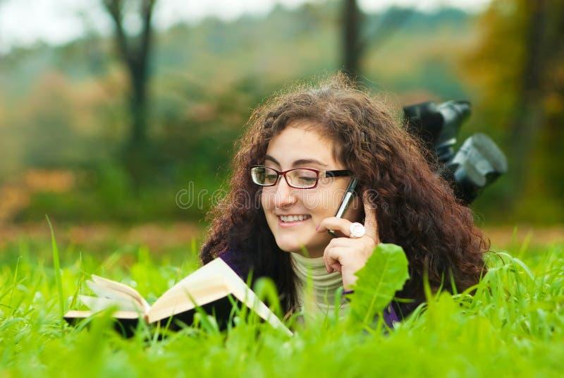 Disposizioni della giovane donna su un'erba fotografia stock libera da diritti