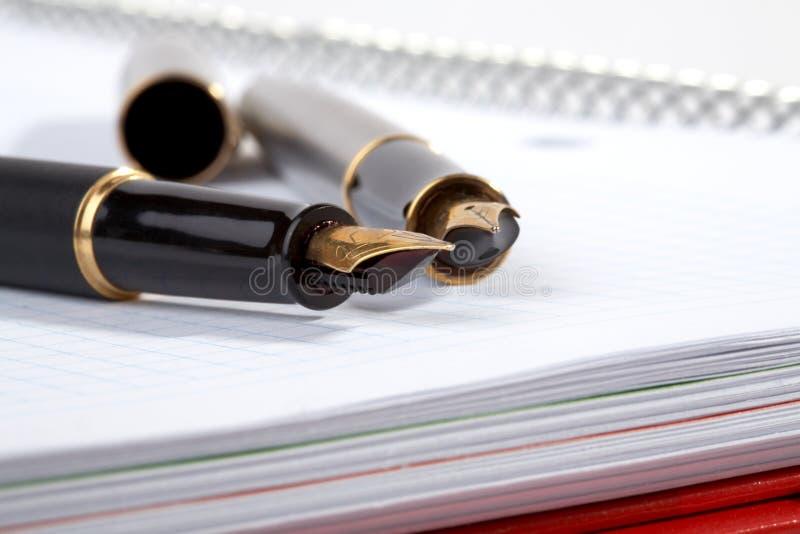 Disposizioni delle penne di fontana su un scrittura-libro fotografie stock