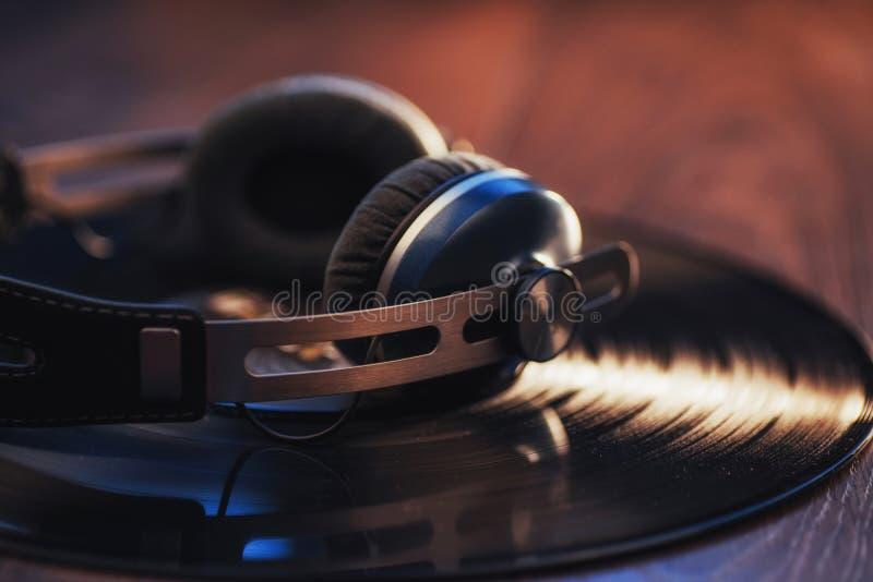 disque vinyle et écouteur au-dessus de table en bois Enthousiaste audio, mélomane ou equipmen professionnels de jockey de disque images stock