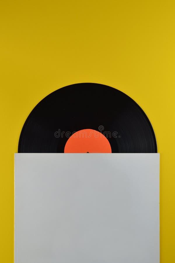 Disque vinyle noir à mi-chemin hors de la couverture blanche photographie stock