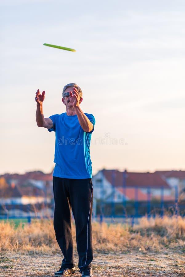 Disque volant de lancement d'homme supérieur en parc photographie stock libre de droits