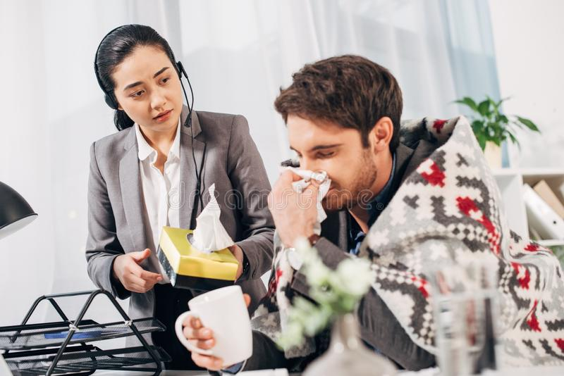 Disquieted call center operator giving napkins to sick coworker with blanket and cup royalty free stock photo