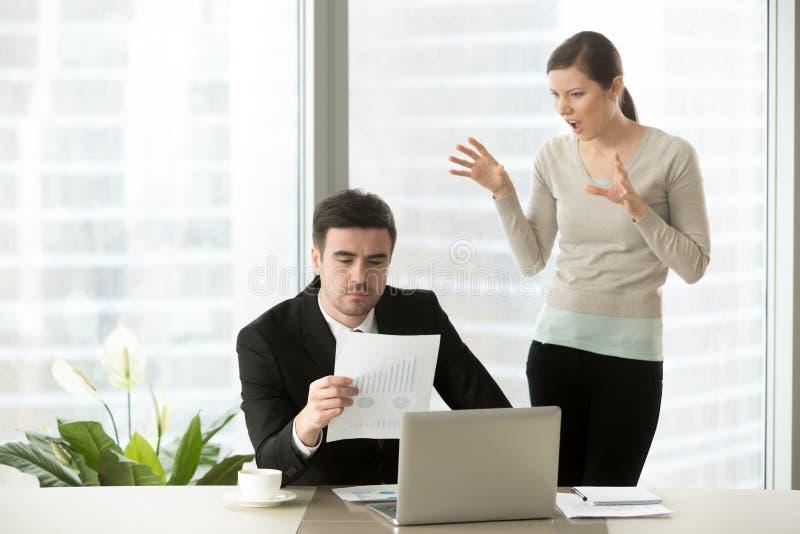 Disrespectful employee grimacing, making faces behind back of se. Female disrespectful employee grimacing standing behind back of serious executive checking stock images