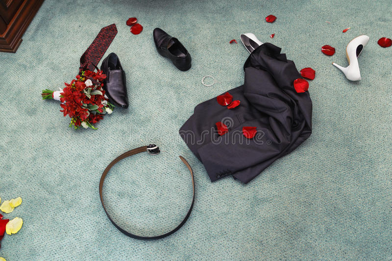 Disrobed wedding clothes. Wedding night. disrobed wedding clothes. straggle objects. Shues, suit, bouquet, belt, necktie and rose petal stock photos