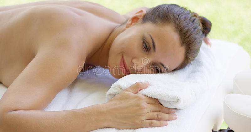 Disrobed woman lays belly down on table. As she relaxes while waiting for masseuse stock photo