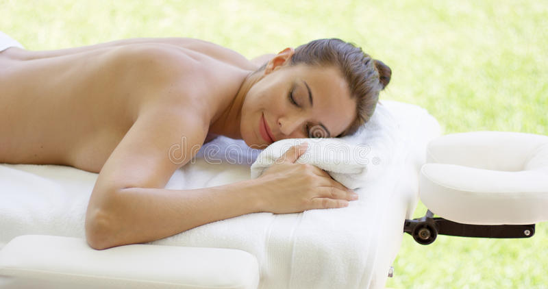 Disrobed woman lays belly down on table. As she relaxes while waiting for masseuse stock image