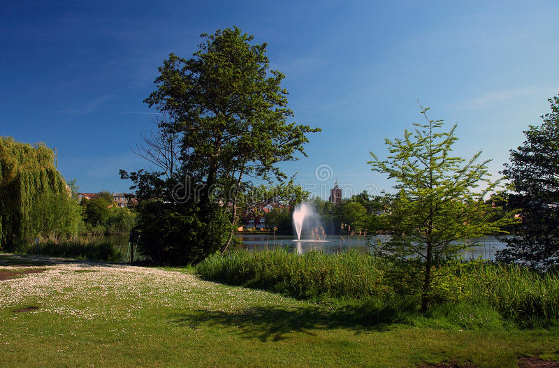 Diss Park Mere and Fountain. My home town Diss Norfolk East Anglia England United Kingdom. Taken during a hot clear blue sky summer's day showing the fountain stock images