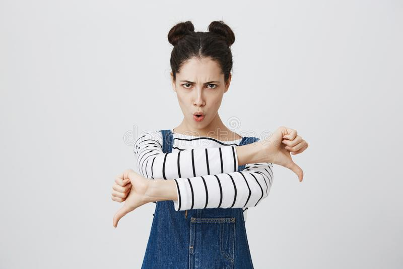 Dissatisfied angry furious girl with hairbuns in denim overalls giving two thumbs down gesture, expressing her. Portrait of dissatisfied angry furious girl with royalty free stock photo