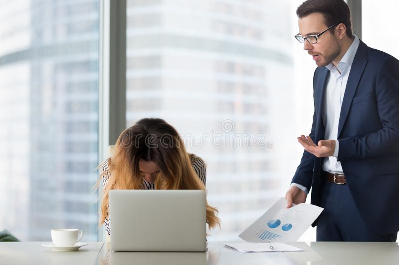 Dissatisfied boss shouting at young desperate woman. stock photography