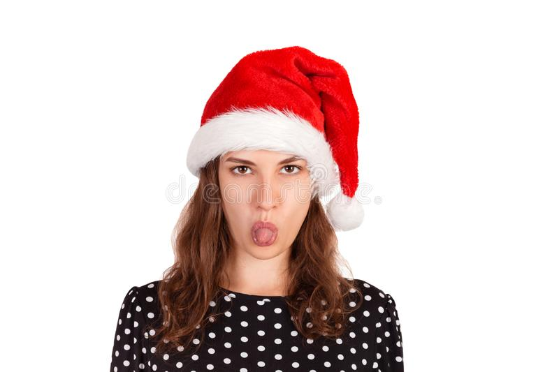 Dissatisfied brunette female model has disgusting expression, shows tongue, irritated with somebody. emotional girl in santa claus royalty free stock photo
