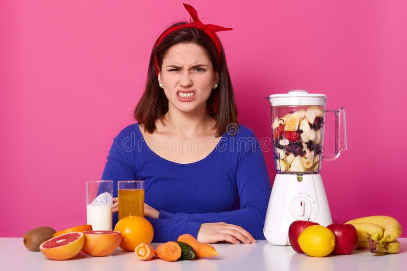 Dissatisfied female model frowns face, wears headband, blue jumper, feels displeased, keeps to diet, makes fruit smoothie or salad royalty free stock photography