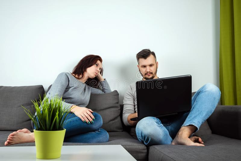 Dissatisfied girl looks like a guy playing in a laptop. The concept of family relationships, problems, misunderstanding, royalty free stock photography