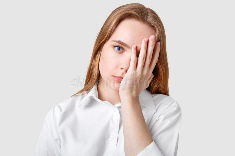 Dissatisfied hopeless blue eyed woman covers face with palm, has long hair, wears elegant shirt, looks stresfully at camera, royalty free stock photo