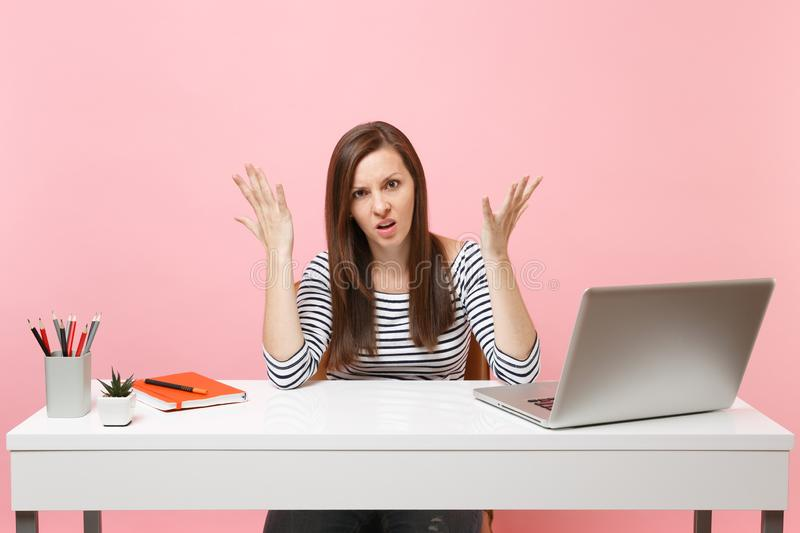 Dissatisfied upset tired woman in casual clothes spreading hand sit work at white desk with contemporary pc laptop stock images